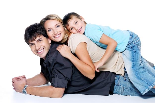 Jonge en gelukkige familie met kind poseren op witte ruimte
