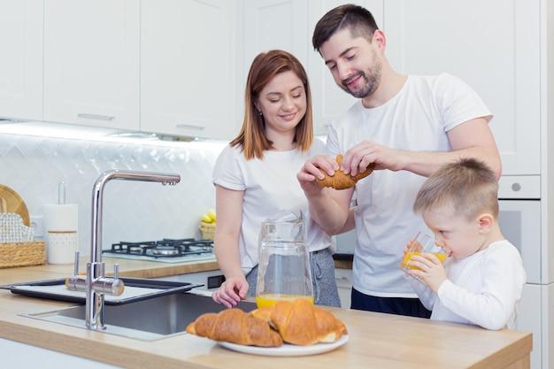 Jonge en gelukkige familie met twee jonge zonen die ontbijt samen in hun keuken voorbereiden