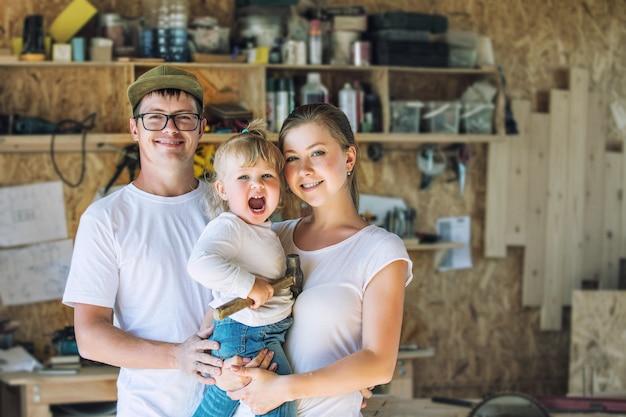 Jonge en gelukkige familie moeder, vader en baby in de timmerwerkplaats werken met tools