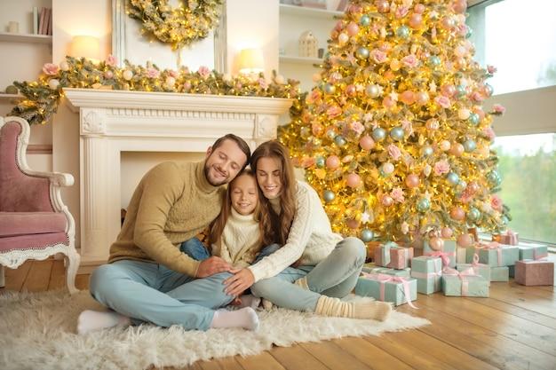 Jonge en gelukkige familie zittend op de vloer in de buurt van de kerstboom en comfortabel voelen