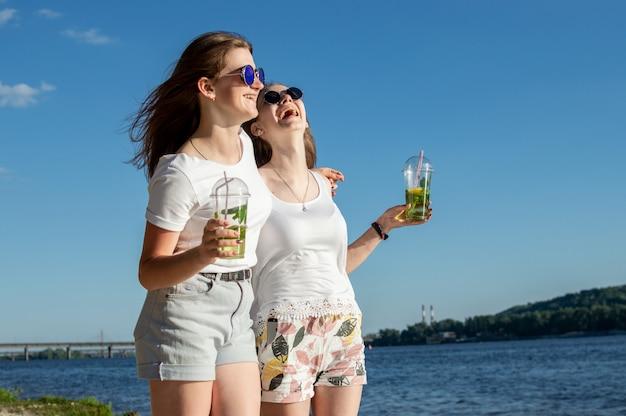 Jonge en gelukkige meisjes lopen langs het strand