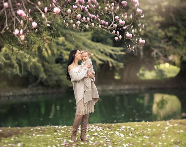 Jonge en gelukkige moeder zorgt voor haar jonge zoon en loopt in de zomer langs de oever van het meer in het park