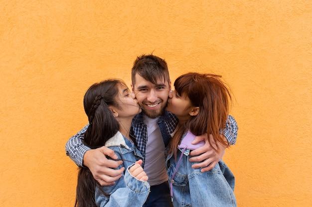 Jonge en gelukkige vader knuffelt zijn kinderen, foto voor vaderdag