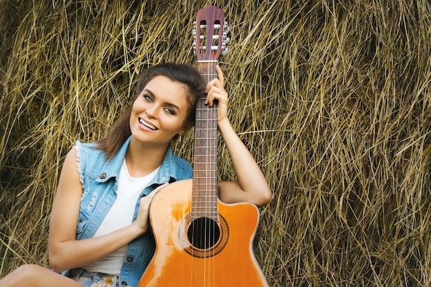 Jonge en gelukkige vrouw gitaarspelen in het dorp