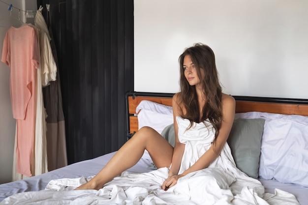 Jonge en gelukkige vrouw ontspannen in het bed