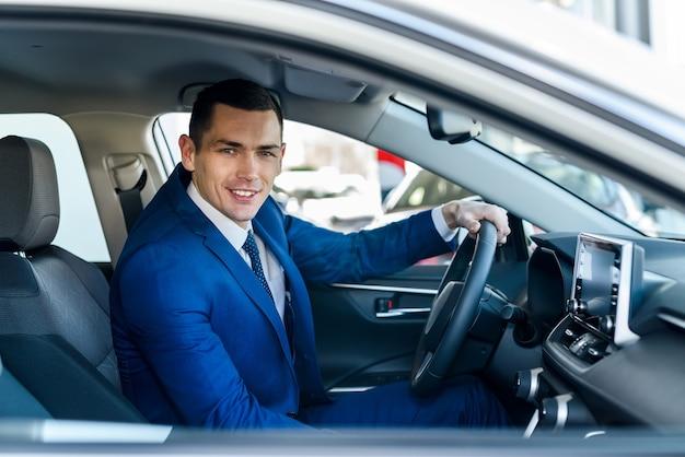 Jonge en gelukkige zakenmanzitting in nieuwe auto in showroom