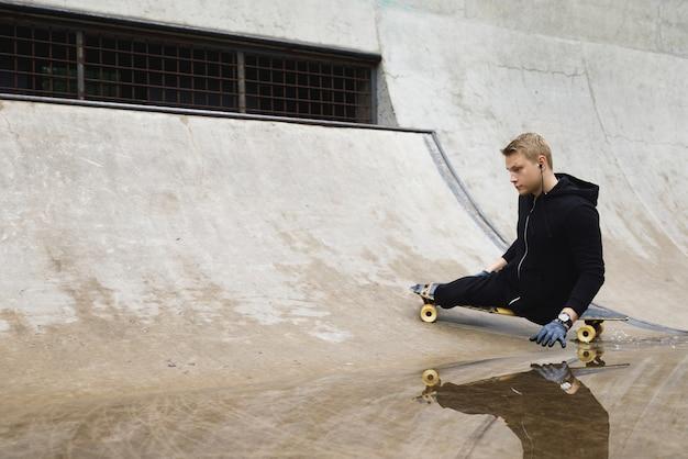 Jonge en gemotiveerde gehandicapte man met een longboard in het skatepark