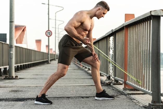 Jonge en gespierde man tijdens de training met een elastiekje weerstand op een straat.