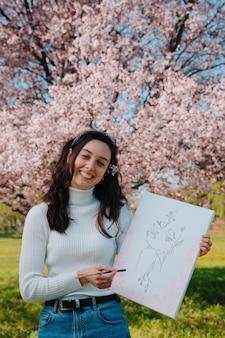 Jonge en getalenteerde vrouw die een vrouw heeft geschilderd