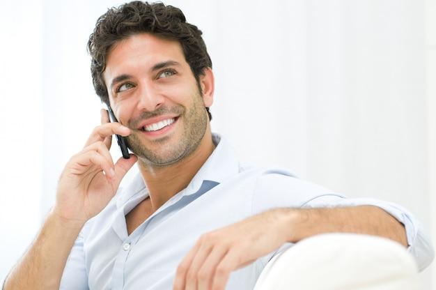 Jonge en gezonde man glimlachend en praten over slimme telefoon thuis