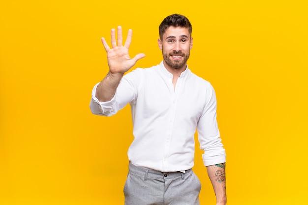 Jonge en handosme mens die vriendschappelijk glimlacht kijkt, nummer vijf of vijfde met vooruit hand toont, die over kleurenmuur aftelt