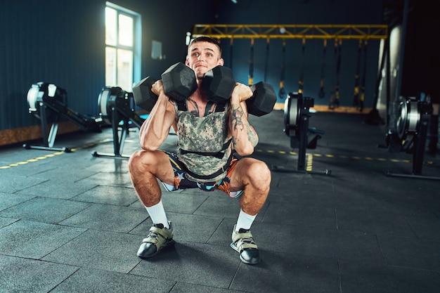 Jonge en knappe atleet man doet oefeningen voor de spieren van de handen van dumbells in de sportschool. crossfit en gezondheidsconcept