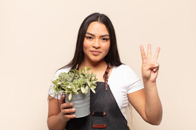 Jonge en latijnse vrouw die vriendelijk glimlacht kijkt, nummer drie of derde met vooruit hand toont, aftellend