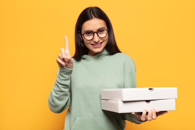 Jonge en latijnse vrouw die vriendelijk glimlacht kijkt, nummer één toont of eerst met vooruit hand, aftellend