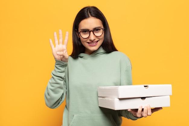Jonge en latijnse vrouw die vriendelijk glimlacht kijkt, nummer vier of vierde met vooruit hand toont, aftellend