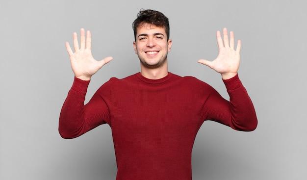 Jonge en mens die vriendelijk glimlacht kijkt, nummer tien of tiende met vooruit hand toont, aftellend