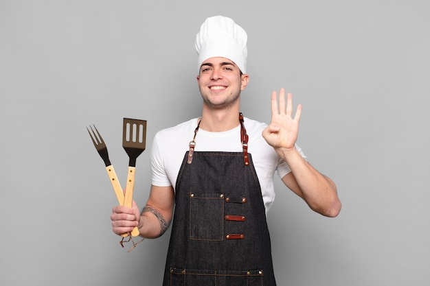 Jonge en mens die vriendelijk glimlacht kijkt, nummer vier of vierde met vooruit hand toont, aftellend