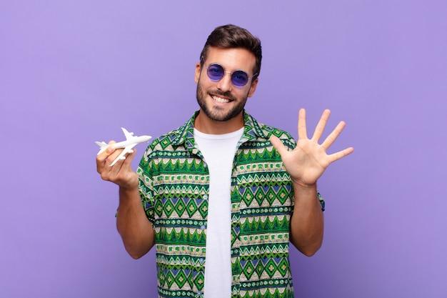 Jonge en mens die vriendelijk glimlacht kijkt, nummer vijf of vijfde met vooruit hand toont, aftellend. vakantie concept