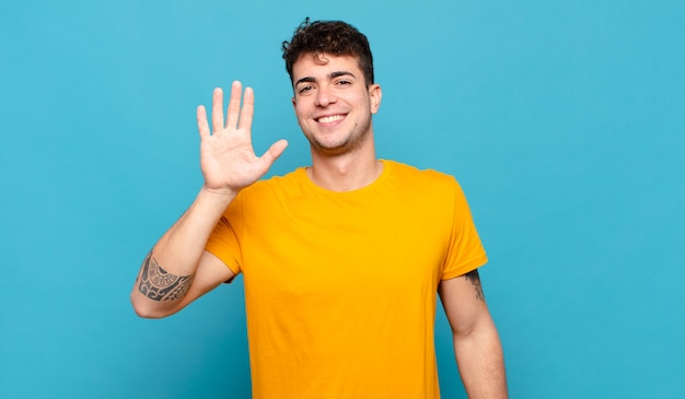 Jonge en mens die vriendelijk glimlacht kijkt, nummer vijf of vijfde met vooruit hand toont, aftellend