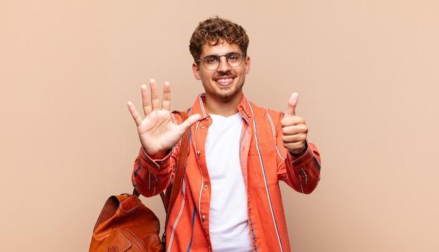 Jonge en mens die vriendelijk glimlacht kijkt, nummer zes of zesde met vooruit hand toont, aftellend. student concept