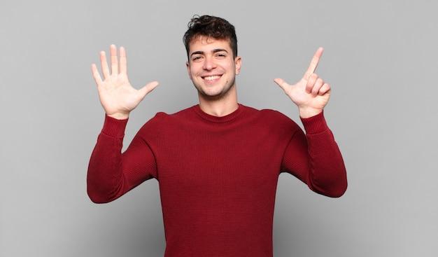 Jonge en mens die vriendelijk glimlacht kijkt, nummer zeven of zevende met vooruit hand toont, aftellend