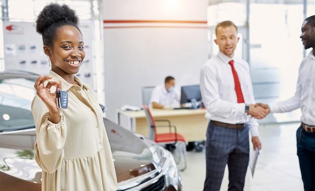 Jonge en mooie afro dame gey sleutels van auto in dealer