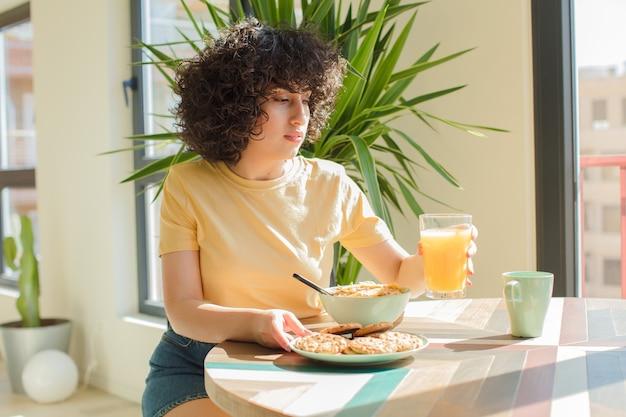 Jonge en mooie arabische vrouw die thuis een ontbijt heeft.