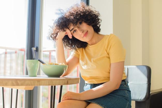 Jonge en mooie arabische vrouw die thuis een ontbijt heeft