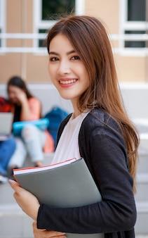 Jonge en mooie aziatische studentenmeisjes die boeken vasthouden, poseren voor de camera met een groep vrienden die op de achtergrond vervagen tegen het schoolgebouw. leren en vriendschap van tieners goede vriend concept.