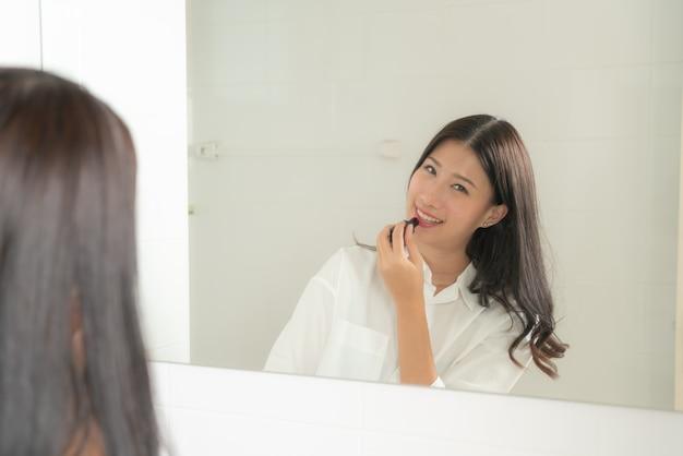 Jonge en mooie aziatische vrouw make-up zelf spiegel kijken