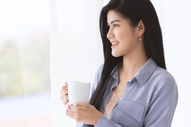 Jonge en mooie aziatische vrouw met witte keramische koffiekopje met ontspannen en gemakkelijk gebaar terwijl je ver naar buiten kijkt met zacht gordijn. idee om 's ochtends gelukkig te zijn.