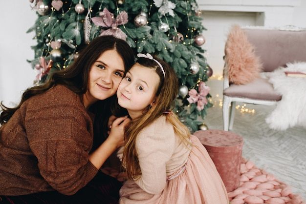 Jonge en mooie blanke moeder knuffelen haar mooie dochter in de buurt van de kerstboom