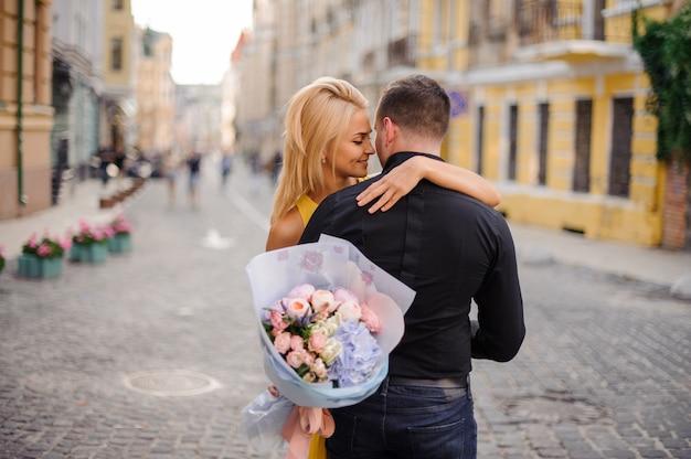 Jonge en mooie blondevrouw die een boeket van bloemen houden en een man koesteren
