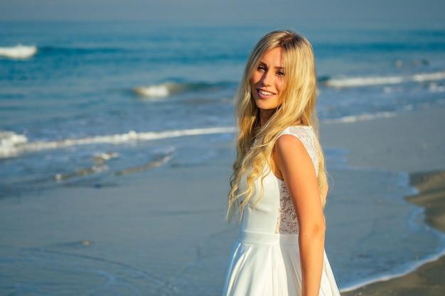Jonge en mooie bruid met lang blond haar die prachtig lacht en op de zee loopt in een mooie witte lange trouwjurk. een gelukkige bruid trouwde met een huwelijksceremonie op het strand aan zee