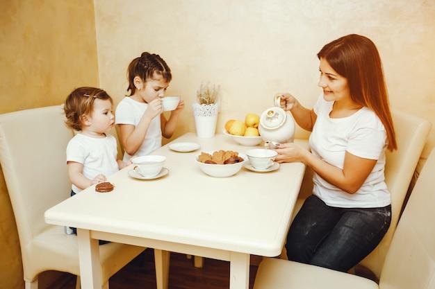 Jonge en mooie moeder in de keuken met haar kinderen die thee met koekjes drinken