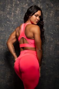Jonge en mooie spaanse bodybuilder-atleet die op haar rug poseert in fuchsia sportkleding