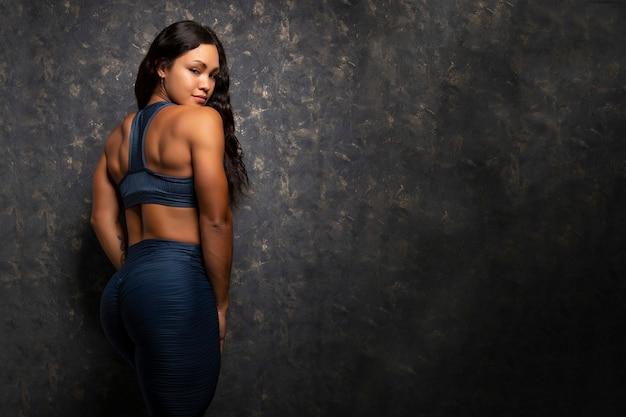 Jonge en mooie spaanse bodybuilder-atleet poseren op haar rug in blauwe sportkleding