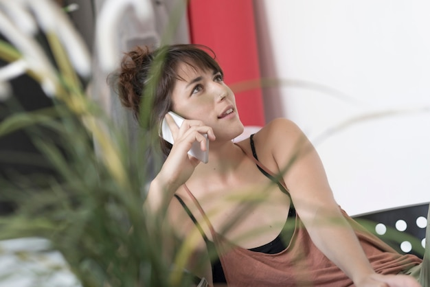 Jonge en mooie startup-werknemer met behulp van een moblie-telefoon