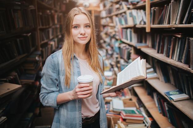 Jonge en mooie student in de bibliotheek. ze houdt een kopje koffie in de rechterhand en een boek in de linker. meisje leest een interessant boek.