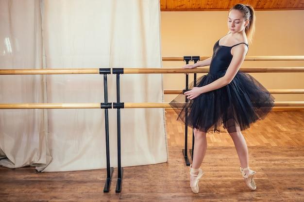 Jonge en mooie vrouw in balletkleding en pointe-dans. de ballerina warmt zich op in de klas. het meisje van de ballerina in een mooie zwarte jurk.