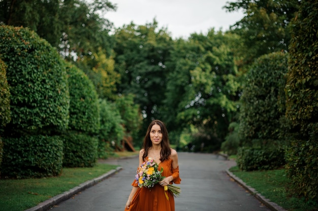 Jonge en mooie vrouw in lange oranje jurk