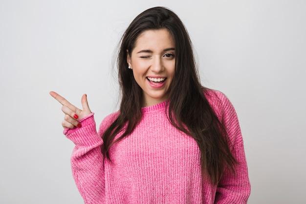 Jonge en mooie vrouw in roze warme trui, natuurlijke uitstraling, glimlachen, wijzende vinger opzij, knipogen, portret aan, geïsoleerd, lang haar, grappige gezichtsuitdrukking, positieve stemming