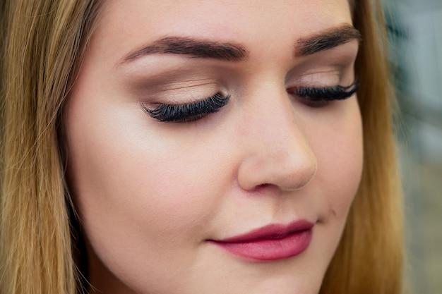 Jonge en mooie vrouw met kunstmatige verlengde zijden wimpers ogen gesloten in een schoonheidsstudio, close-up perfecte huid.