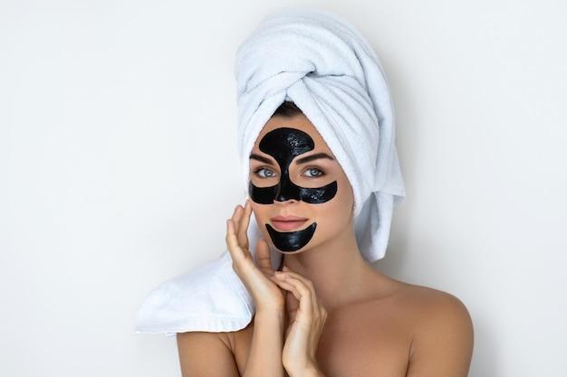 Jonge en mooie vrouw met zwarte peel-off masker op haar gezicht