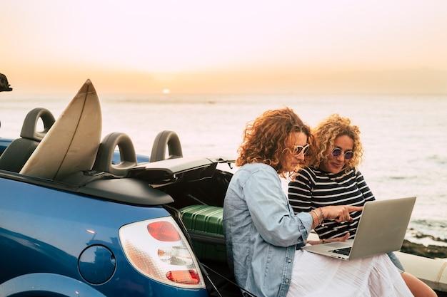 Jonge en mooie vrouwen genieten van reizen en technologie zwerven met de auto