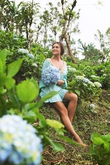 Jonge en mooie vrouwenbloemist die hydrangea hortensiabloemen in het gebied verzamelen