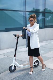 Jonge en mooie zakenvrouw rijdt elektrische scooter in de stad