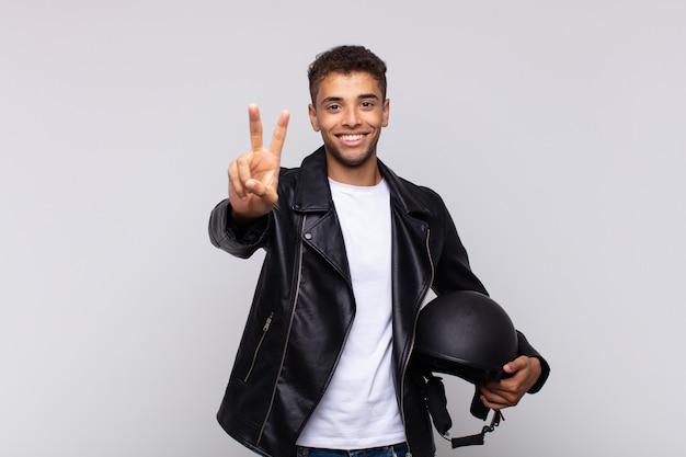 Jonge en motorrijder die vriendelijk glimlacht kijkt, nummer twee of seconde met vooruit hand toont