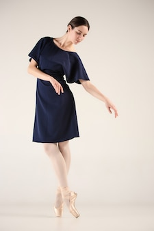 Jonge en ongelooflijk mooie ballerina danst in een blauwe studio
