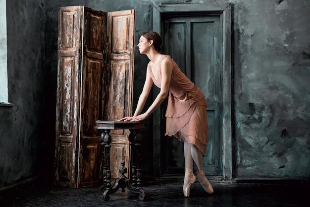 Jonge en ongelooflijk mooie ballerina poseert en danst in een zwarte studio